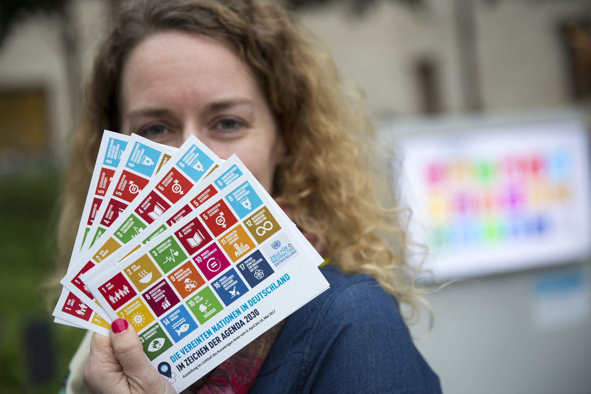 Woman holding cards showing the 17 Sustainable Development Goals (SDGs)
