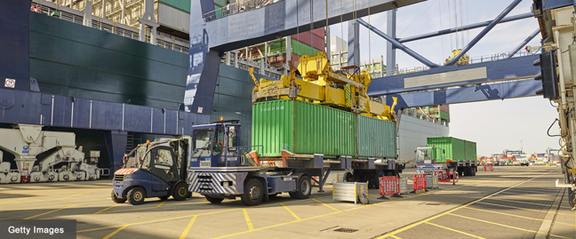 Photo of a truck being loaded with container at cargo port