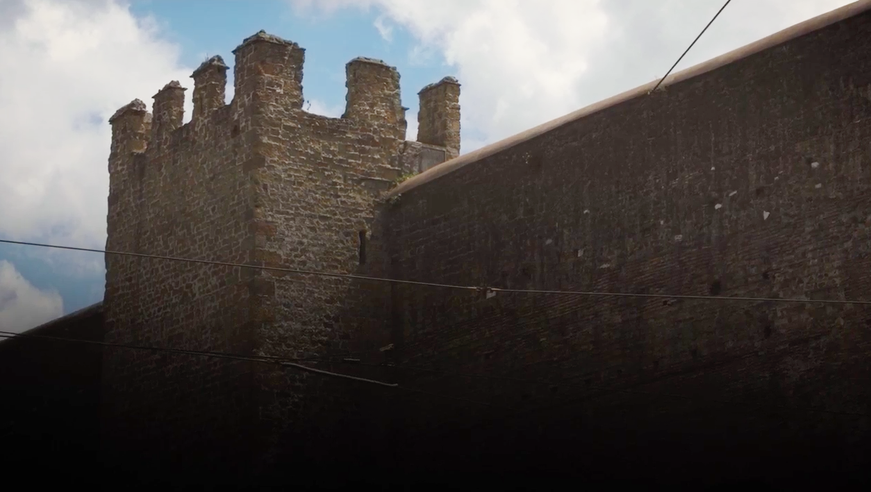 Part of a enormous grey brick wall with a large turret
