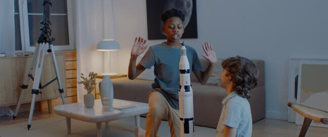 Two children playing with a toy rocket