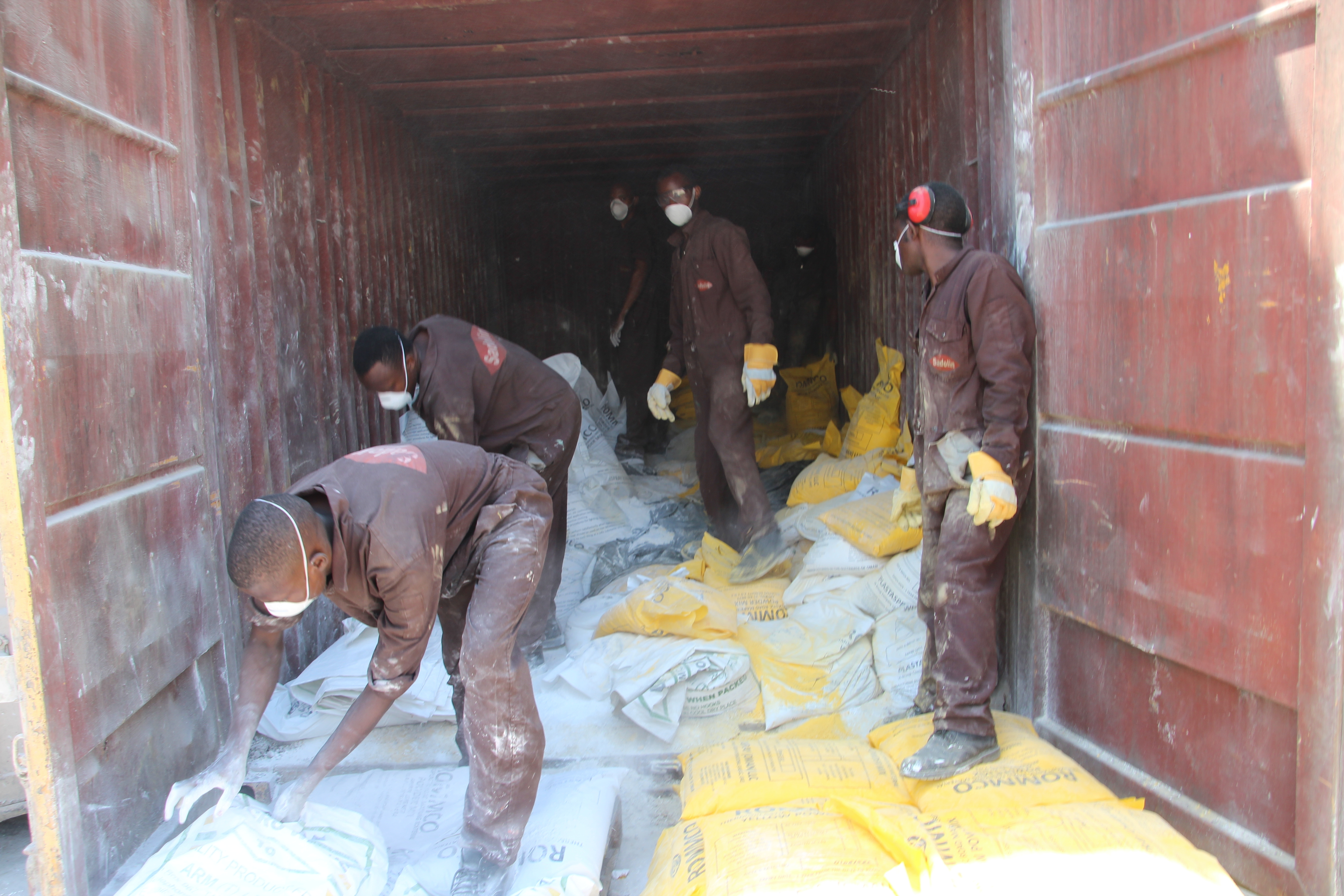 Workers handling bags of powder used for making paint