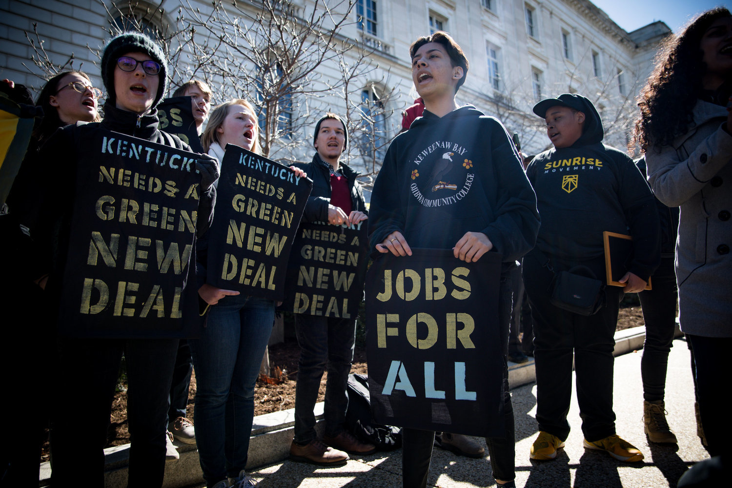 Protesters with placards with slogans including 'jobs for all', Kentucky needs a green new deal',