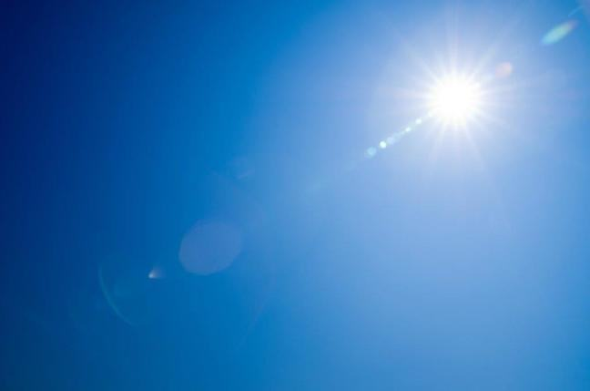Photograph of the Sun shining in a blue sky