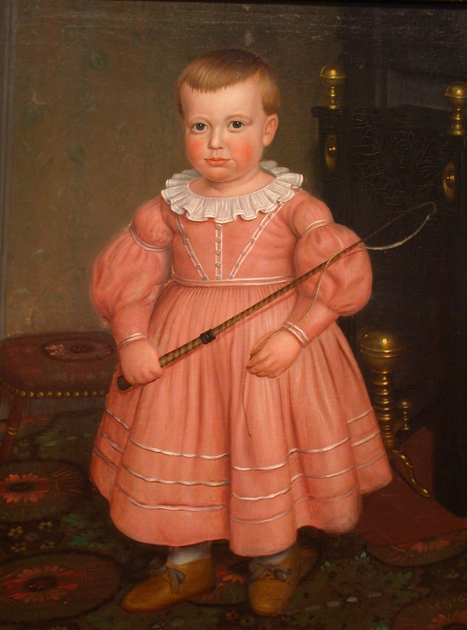 A seventeenth century portrait of a small boy, holding a whip. He is wearing a pink dress