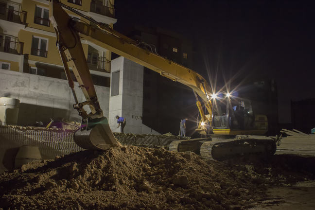 Construction workers working night shift using excavator