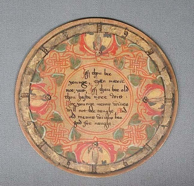 A mid 16th century roundel made from oak and sycamore. It is painted, silvered and varnished with patterns and images of plant life, as well as some writing in the centre.