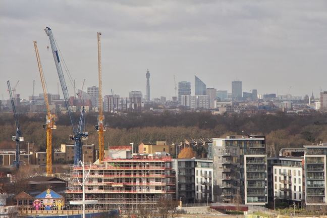 Photo of construction work on high rise buildings, cranes, with trees in the background