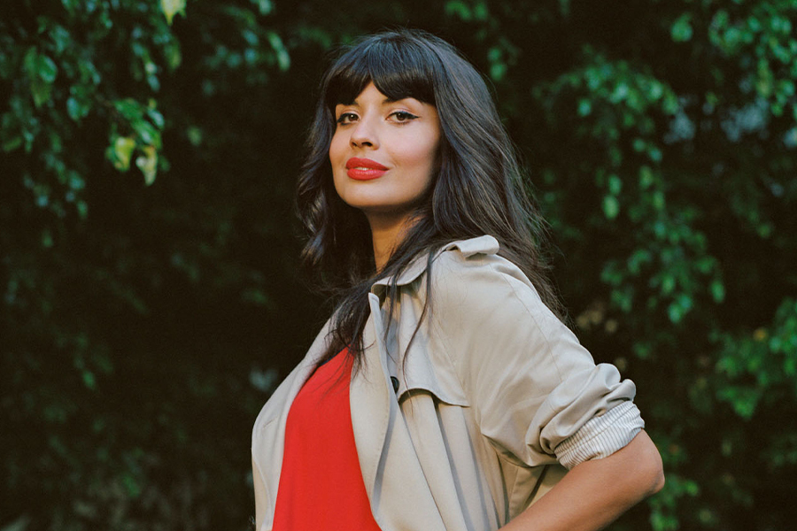 A photograph of Jameela Jamil wearing a light brown coat, red dress with matching red lipstick and long, dark brown hair. Jameela poses in front of some greenery