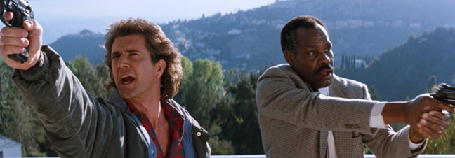 Lethal Weapon film still, actors Mel Gibson and Danny Glover armed with guns outside a house. Danny Glover looks nervous, Mel Gibson more confident.
