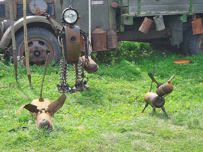 A photograph of a garden with recycled metal objects depicting a person and two playing dogs. The person could be a veterinarian.