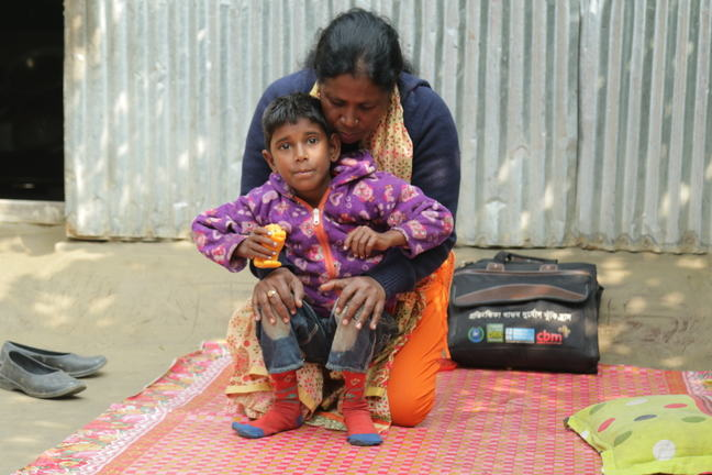 A boy being supported through physiotherapy. He is sitting on the therapist's knees.