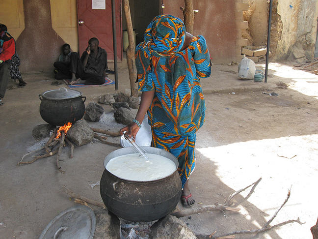Picture of a woman heating milk.
