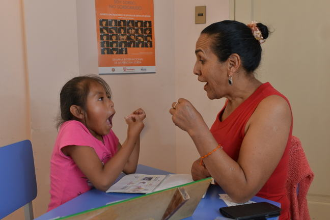 A girl is sitting opposite a woman. The girl is gesticulating as she learns sign language. She is gesturing with her hand and making a shape with her mouth.