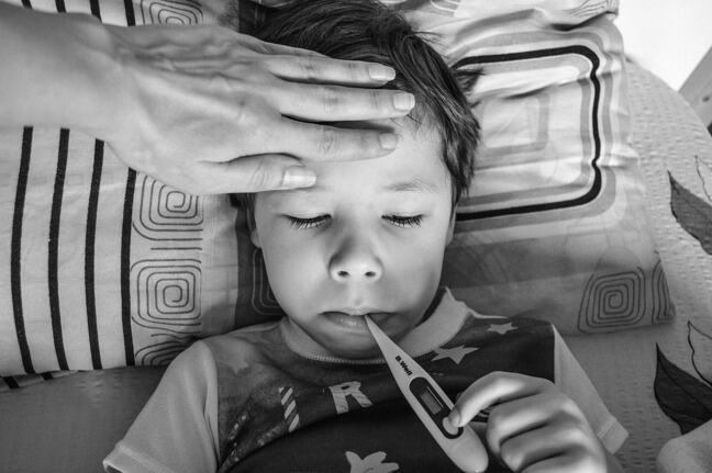 black and white image of a child with a thermometer in mouth