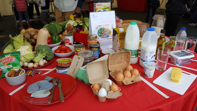 A large selection of food laid on a table which include milk, vegetables and pulses