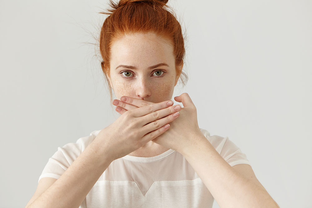 Portrait of serious young ginger European woman covering mouth with both hands keeping a secret