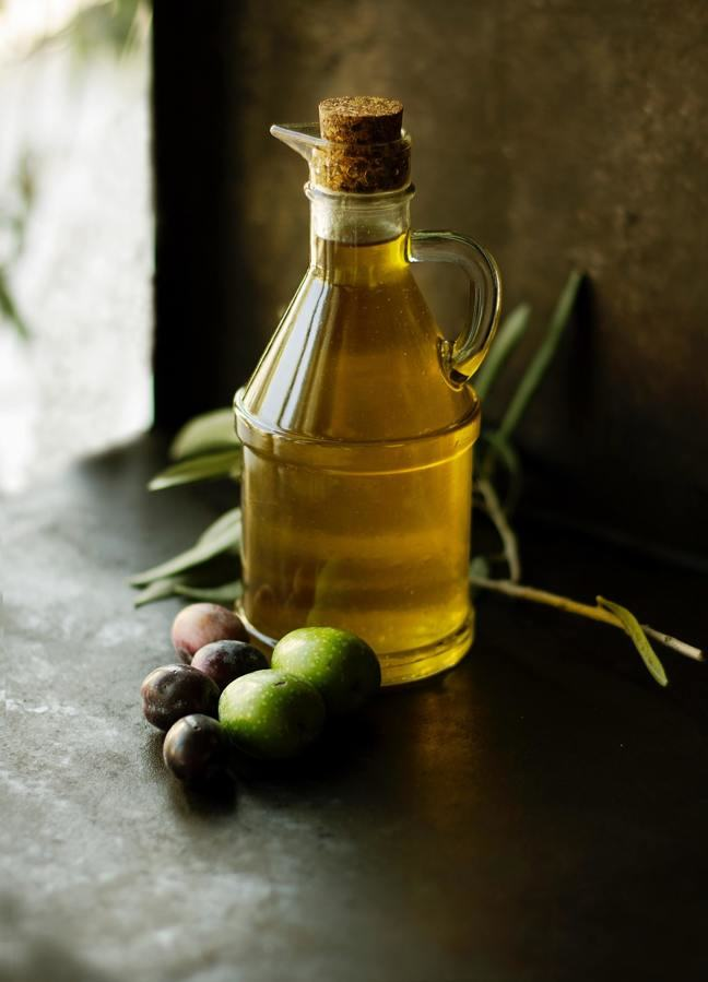 a cork-stoppered glass bottle containing yellow oil on a wooden table with black and green olives in the foreground