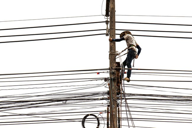 Worker in power tower (electricity pylon)
