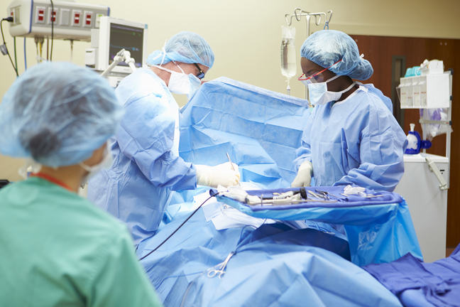 Surgeons using gloves, surgical mask and eye protection to protect themselves from contagious agents during surgery