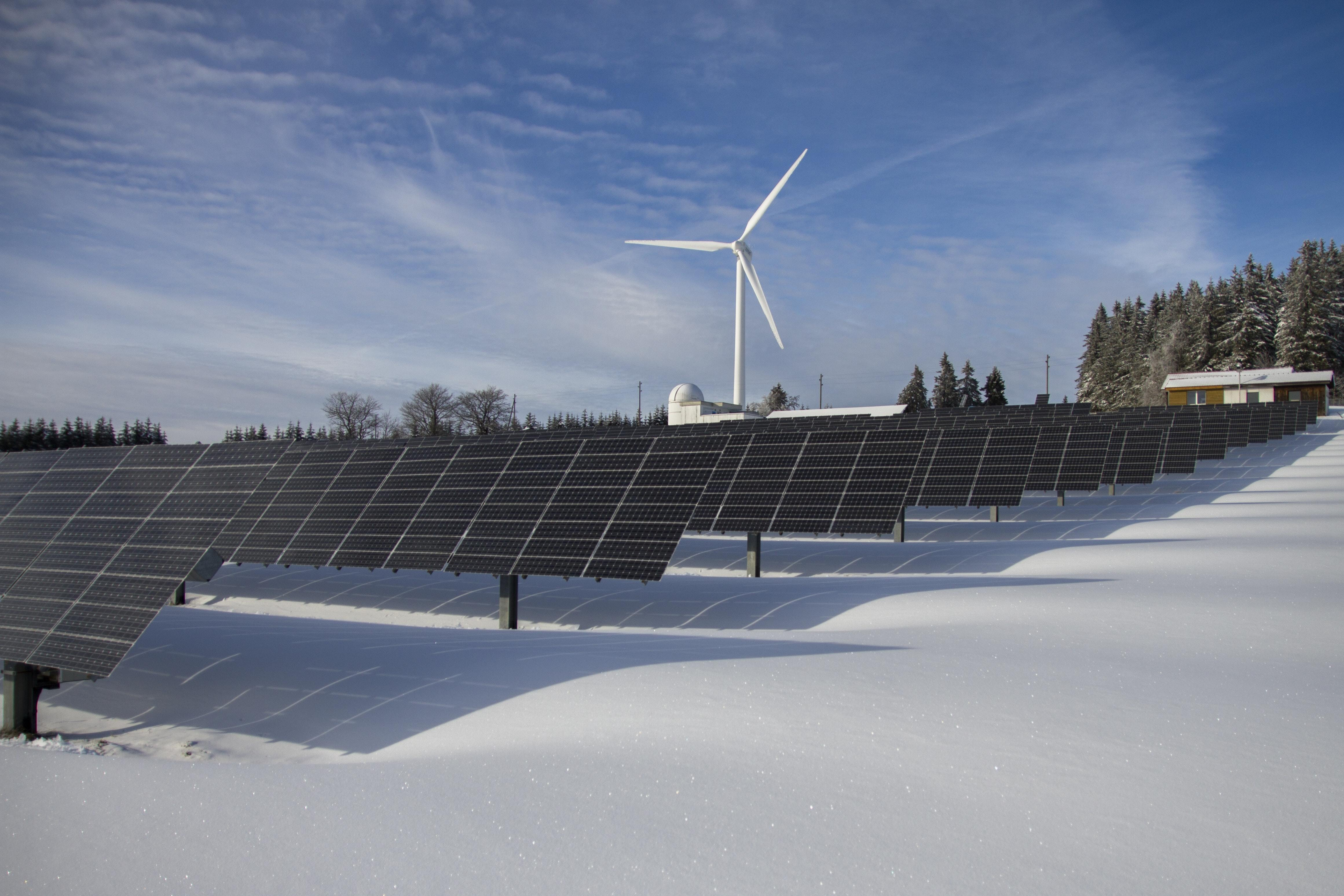 A snow-covered farm covered in rows of solar panels. In the background, a windmill.