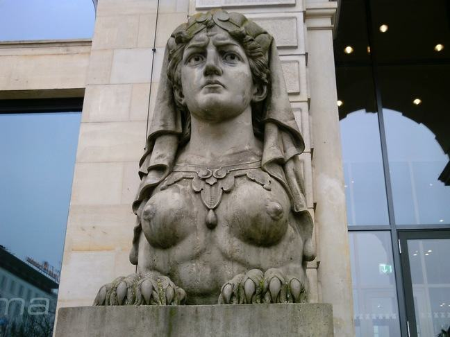 This photograph is a closeup of a stone statue resting on a plinth. The statue features a woman's head and chest, with the breasts exposed, sitting on top of an animal's body similar to that of a lion. The lower half of the statue features claws prominently.