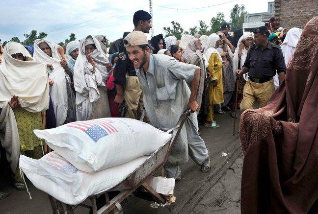 Photograph of Pakistani flood survivors queuing for food at the UNHCR camp in Khyber Pakhtunkhwa province's Charsadda district on August 3, 2010