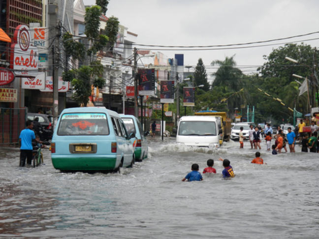 children swimming in flooded street