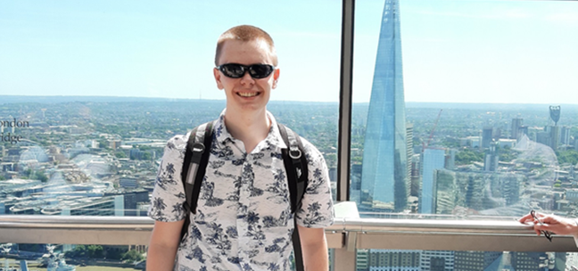 A young man wearing sunglasses and a backpack is smiling towards the camera as he stands on a viewing platform overlooking London on a sunny day.