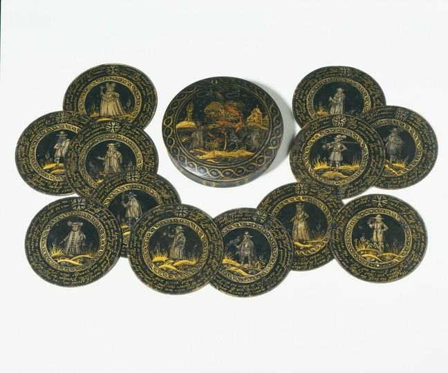 A display of several richly decorated black and gold trenchers