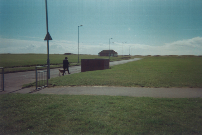 This underexposed photograph shows a sunny beachfront pathway. In the mid-distance a woman is walking her dog.
