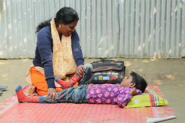 A boy lying on his back as a woman supports him through a physiotherapy session. She is stretching his leg.