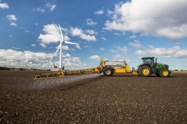 A tractor pulling a wide sprayer across a soil covered field