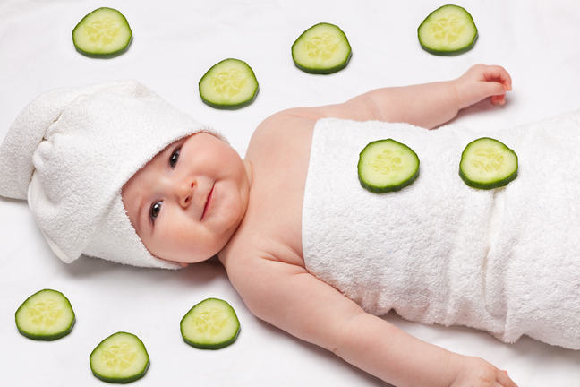 A comical image of a newborn baby wrapped in a towel. She lies back with a towel swaddled around her head as though she is in a beauty salon and there are pieces of cucumber all around her, as though she is in a spa environment