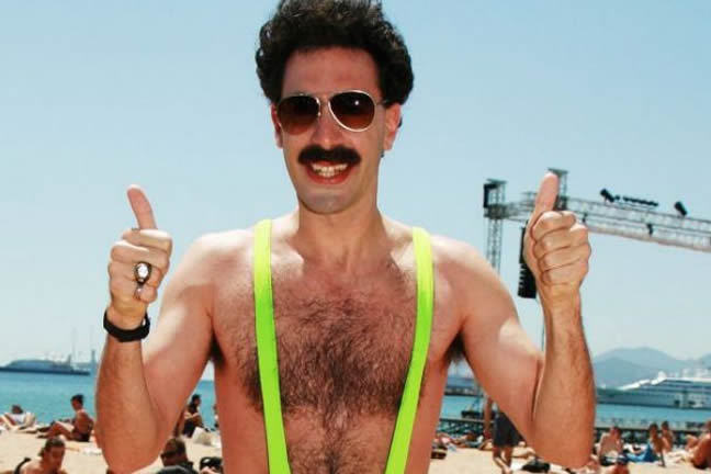 Sacha Baron Cohen as Borat in the film of the same name. He wears a bright yellow man-kini on a hot beach. He looks towards the camera with both thumbs up