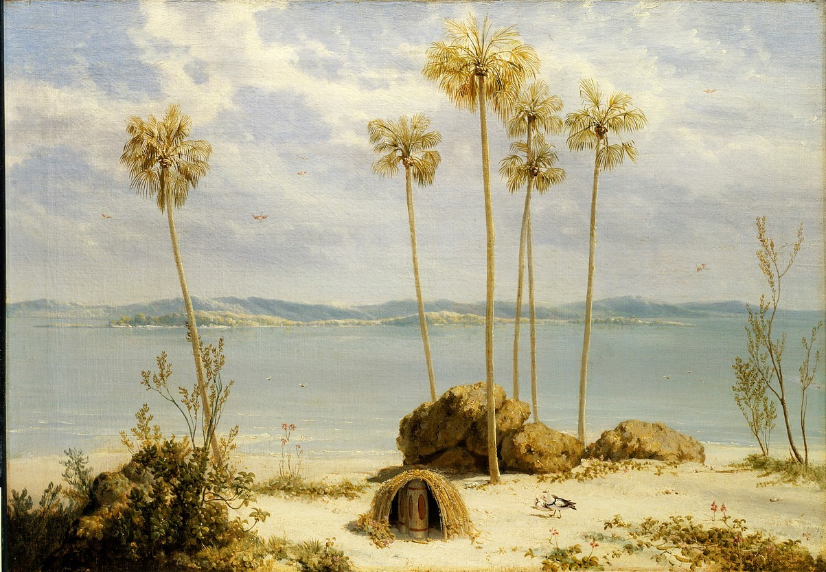 View of blue sea and sky with sand dunes in foreground and a small hut-like structure beneath palm trees containing a cylindrical object with markings