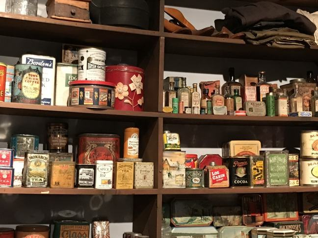 photograph of an old fashioned grocery store with wooden shelves containing numerous different cans, bottles and tins