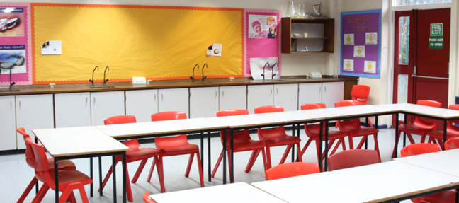 Classroom tables for main seating in a lab space. Limited services at the back and side of the room.