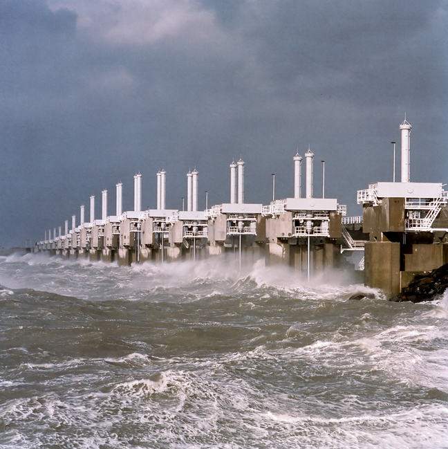 One of the three movable barrier sections of the Oosterscheldekering visible during a storm, with waves crashing against it