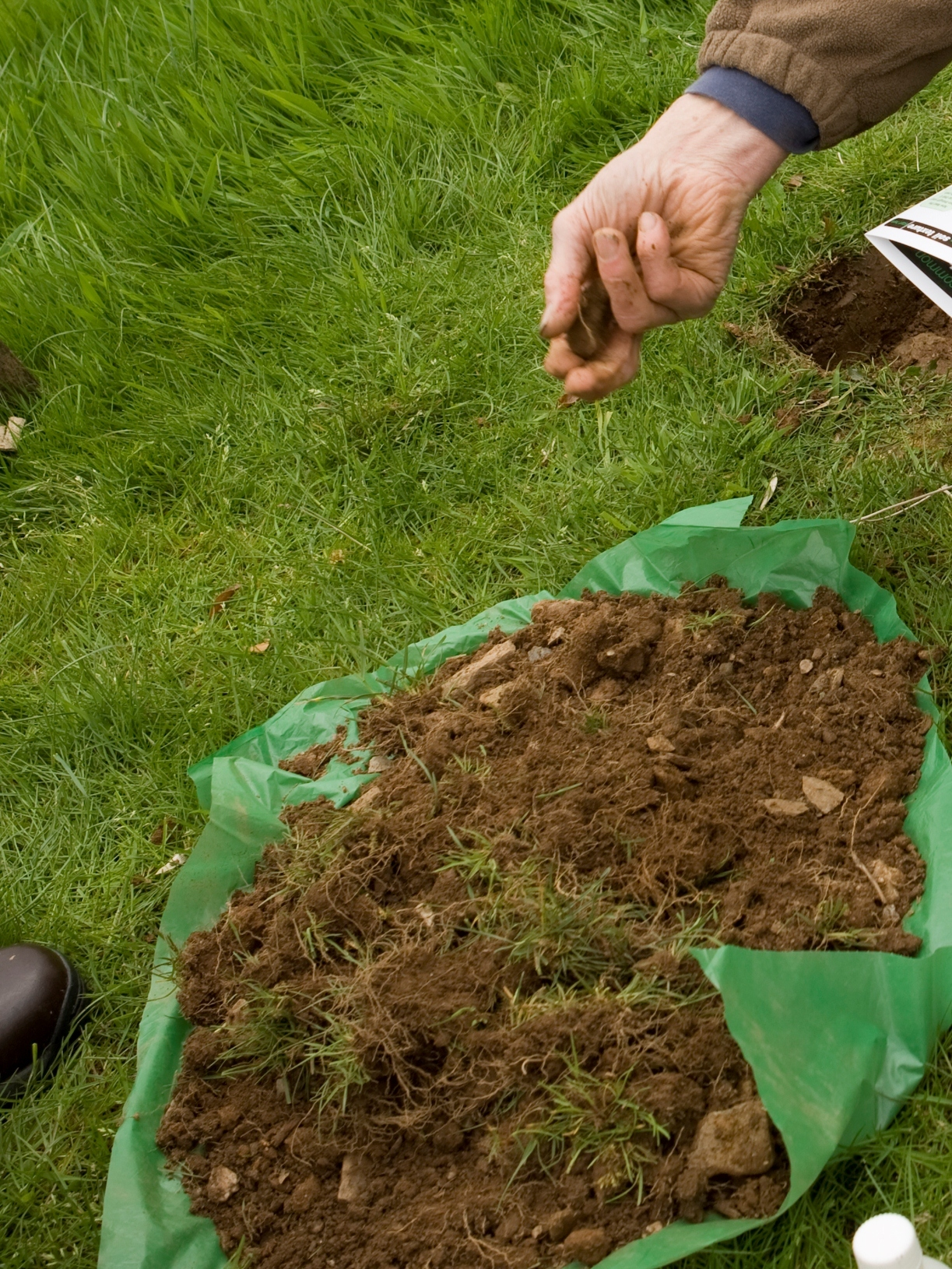 Freshly dug soil, on a piece of green polythene, with a hand crumbling it