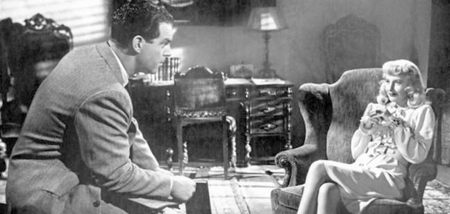 A still from a black and white film. A domestic living room scene. Walter perches, looking at Phyllis who sits comfortably in an arm chair.