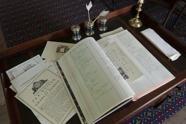 An open ledger on top of menus for the royal family at a desk in Kew Palace