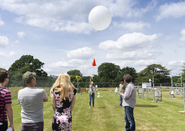 A large balloon on a string is up in the air, being held in place by a student as a amall group of parents of other students look on