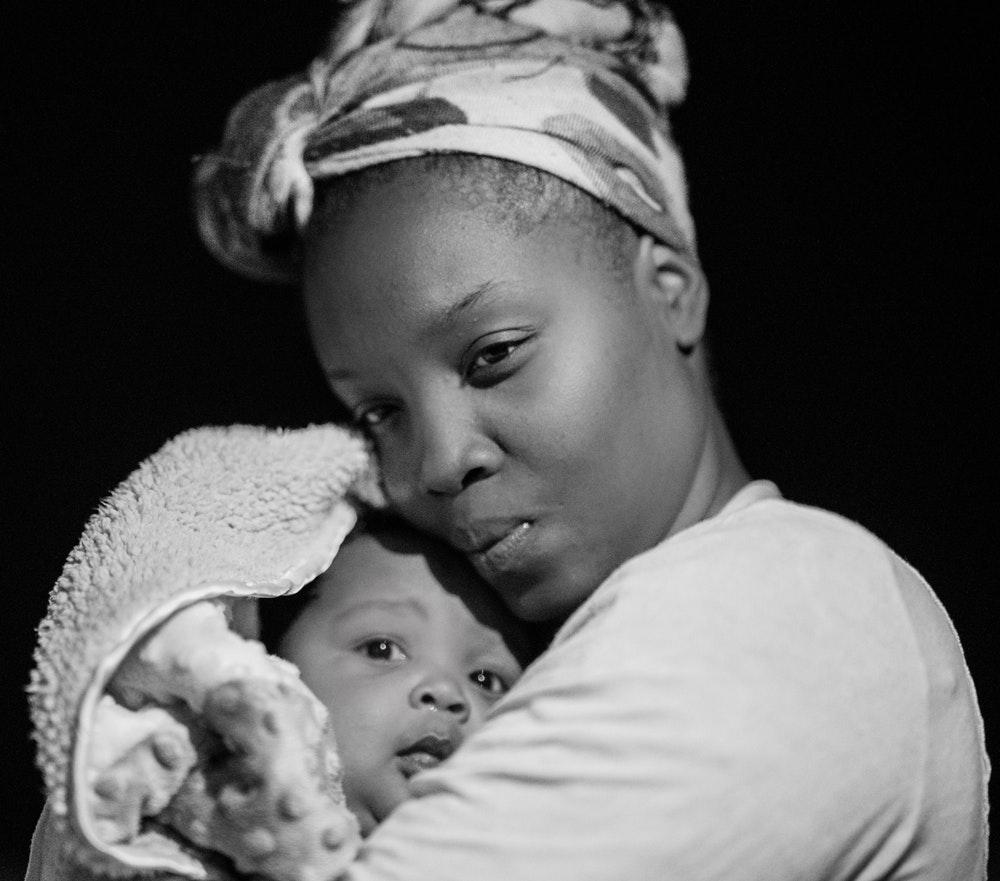 Photo of a black woman cradling a baby