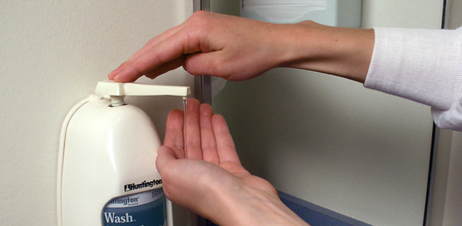 hand using sanitiser pump