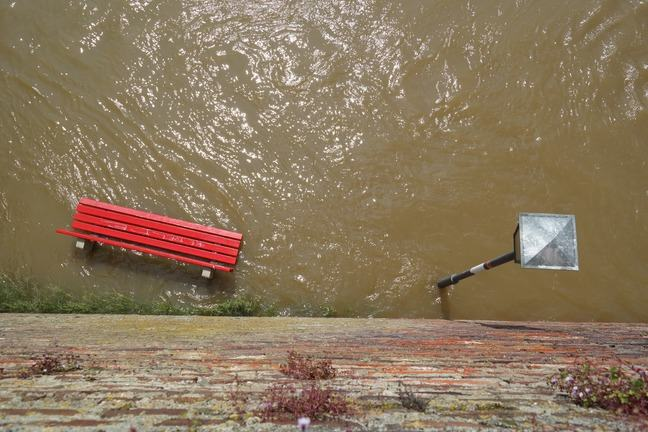 A scene of flooding, with a bench and lamp post submerged in water.