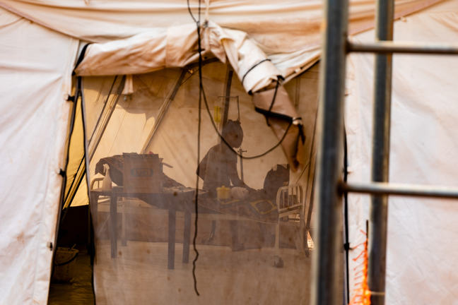 """""""A white coloured tent is shown in the picture. In the entrance is a net door, with black strings hanging from it. Inside the tent is a woman sitting on a bed with her back facing the door, but her face is turned towards the door. On the left side of the bed is an intravenous bag and line hanging from a stand. On the right side of the bed is a table with a box on top of it."""""""
