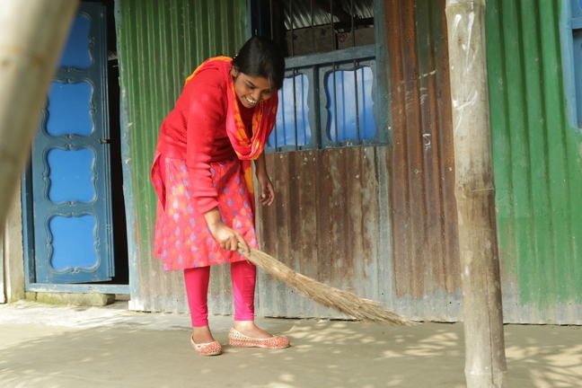 A teenage girl is sweeping outside her home as she smiles.