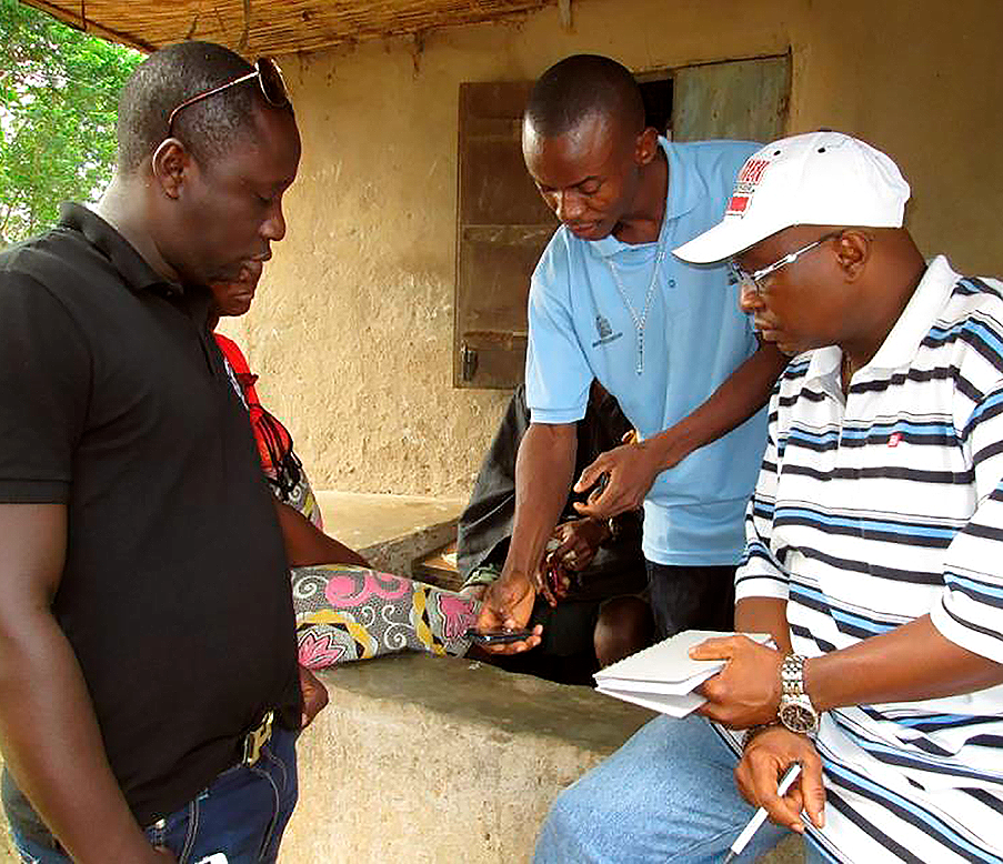 A CHW [Hashiru Jalloh] demonstrating the use of the MoTECH Suite application to a Ministry of Health Official [Sidie Yayah Tunis – Director of ICT in the MoH] and a Ministry of Information and Communication Official [Ambrose Levi – Deputy Director, Policy & Planning] during their field visit to assess the application. December 3-4, 2013; Imperi, Bonthe District