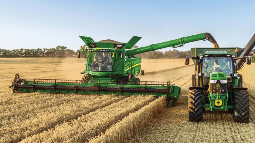 Combine harvester funneling harvested crops into a tractor as it works through the field