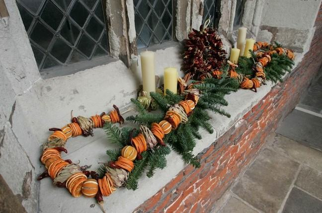 A festive garland of evergreen with dried citrus, sitting on a windowsill